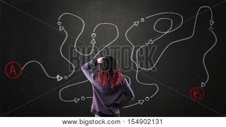Thoughful teenager and a blackboard with drawing of a path from point a to point b