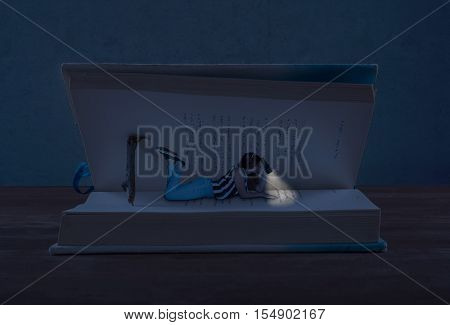 Young girl laying on a open book using a flashlight to read the book in the middle of the night.