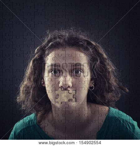 Puzzle of a woman and a missing piece in place of her mouth suggesting censorship