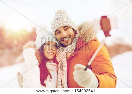 people, season, love, technology and leisure concept - happy couple taking picture with smartphone on selfie stick over winter background