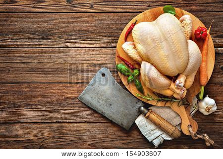 Raw chicken with cleaver and spices on wooden background
