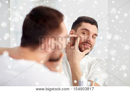 beauty, hygiene, skin problem and people concept - young man looking to mirror and squeezing pimple at home bathroom over snow