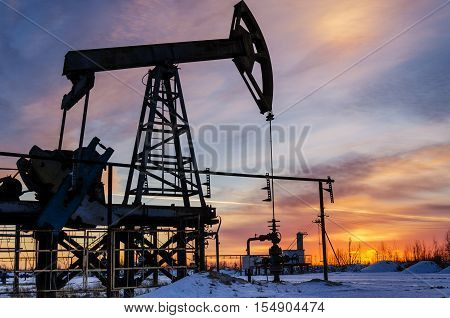 Oil pump wellhead pipeline silhouette during sunset at the oilfield. Winter time. Oil and gas concept.