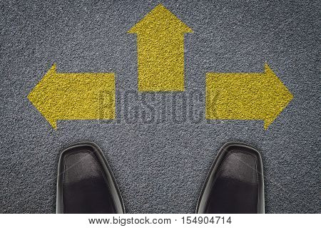businessman standing in front of three arrows on asphalt road business concept to success.