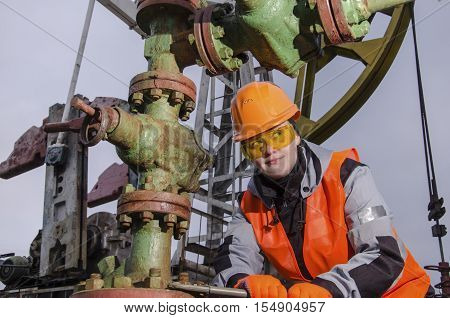 Woman engineer in the oilfield repairing wellhead with the wrench wearing orange helmet and work clothes. Oil rig background. Oil and gas concept.