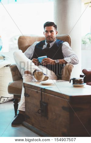 Portrait of good-looking man with blue cup sitting on arm-chair