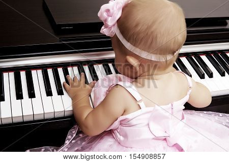 Beautiful baby girl's hands on the keyboard of the piano