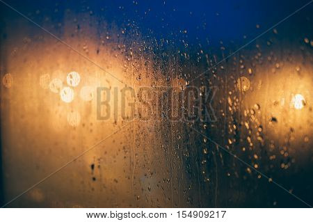 Abstract background of blurred lights through steamy window with waterdrops selective focus