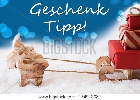German Text Geschenk Tipp Means Gift Tip. Moose Is Drawing A Sled With Red Gifts Or Presents In Snow. Christmas Card For Seasons Greetings. Blue Background With Bokeh Effect.