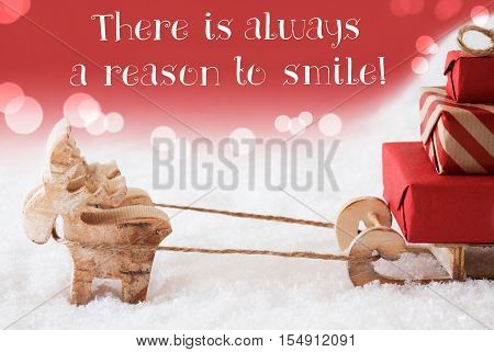 Moose Is Drawing A Sled With Red Gifts Or Presents In Snow. Christmas Card For Seasons Greetings. Red Christmassy Background With Bokeh Effect. English Quote There Is Always A Reason To Smile