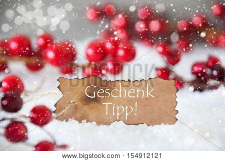 Burnt Label With German Text Geschenk Tipp Means Gift Tip. Red Christmas Decoration On Snow. Cement Wall As Background With Bokeh Effect And Snowflakes. Card For Seasons Greetings