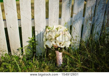 Wedding Bouquet On White Fense On Ceremony Place