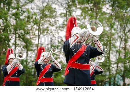 Military fanfare playing at trumpet and other wind instruments for occasion.