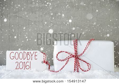 One Christmas Present On Snow. Cement Wall As Background With Snowflakes. Modern And Urban Style. Card For Birthday Or Seasons Greetings. Label With English Text Goodbye 2016 For Happy New Year