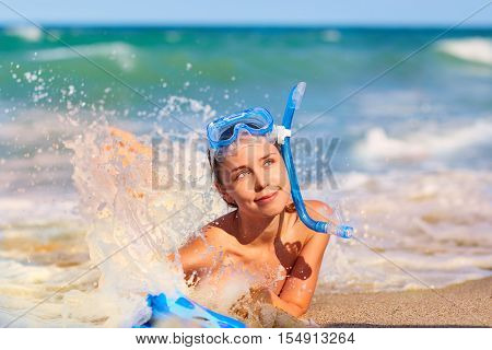 Concept summer totdyha sea ocean travel. Beautiful young girl on the beach wearing a scuba diving lying on the beach beautiful splashes of water.