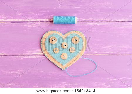 How to sew a felt heart decor. Step. Join the felt edges of felt heart with blue thread. Blue thread, needle on wooden background. DIY idea for Valentine's day, wedding, mother's day. Top view