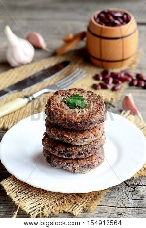 Fried bean cutlets with garlic and spices on a plate. Small decorative barrel with uncooked red beans, garlic, parsley, fork, knife on wooden background. Healthy diet cutlets. Rustic style. Closeup