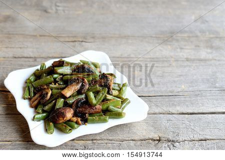 Fried green beans with mushrooms and spices on a plate and on old wooden background with copy place for text. Vegetarian warm green beans and mushrooms salad recipe. Rustic style