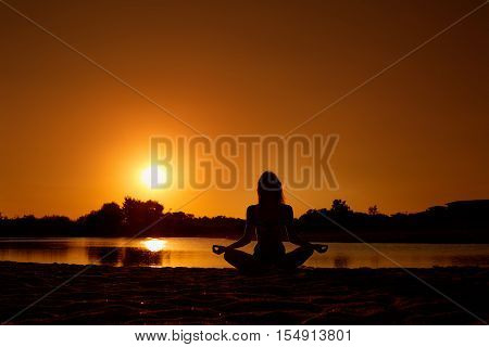 The Concept Of Yoga, Harmony, Meditation, Health. Silhouette Of A Girl In Lotus Position, Meditating
