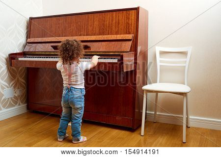 Back view. A child stands in front of the piano and plays a melody. Little pianist learning to play the piano. Baby child kid and music concept.