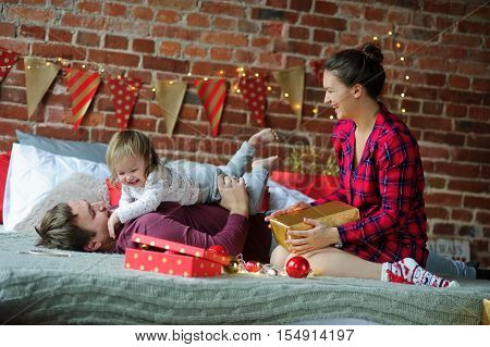 Christmas morning. Young family gleefully congratulates each other Marry Christmas. On a bed there are many Christmas gifts in bright packings. Dad playing with his little daughter.