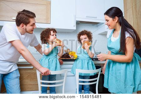Twins Girl With Her Parents In The Kitchen Eating Buns. A Happy Family. Mom, Dad, Sister Twins Happy
