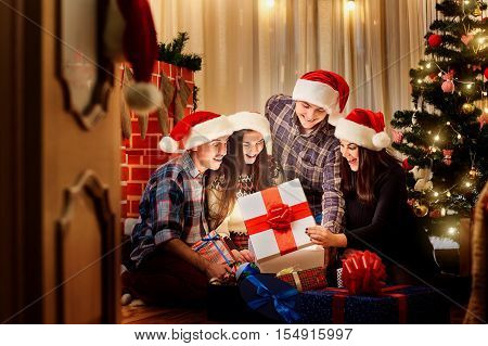 In a group of friends in christmas hats on the floor in the room to open presents with the Christmas tree. Magic light out of the box with a gift in a happy New Year.