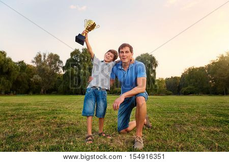 The Son Of A Champion With A Gold Cup Champion With His Father In The Park Embracing Outdoors In Nat
