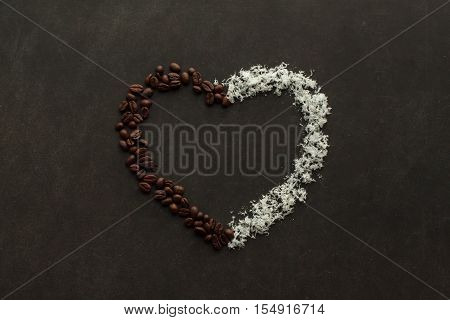 Heart made of coffee beans and coconut chips on the dark background with free space to write down.