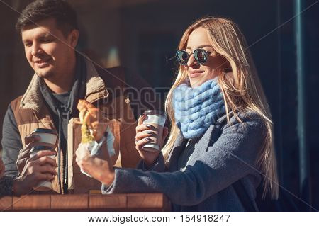 beautiful young woman enjoying her lunch croissant with coffee while she standing outdoors cafe and communicate with friends. The weather is great and sunny!