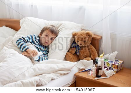 Sick Child Boy Lying In Bed With A Fever, Resting