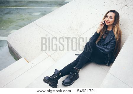 Beautuful smiling young teenage girl is sitting on the concrete steps and talking by phone. Student in alternative style clothes - black leather jacket and big boots. Copy-space area for your advertisement text or design