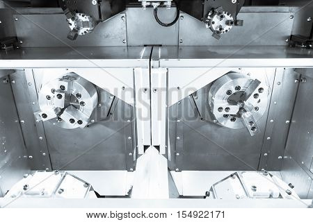The twin spindle of CNC lath machine with out the part in the silver tone effect.