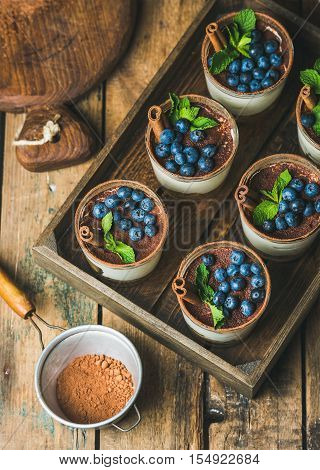 Homemade Tiramisu dessert in glasses with cinnamon, mint and fresh blueberries in wooden tray and sieve with cocoa powder over rustic wooden background, top view, selective focus, vertical composition