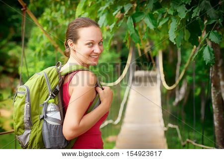Hiking woman - hiker walking on bridge in rain forest. Hiker. Woman hiking smiling happy on trek with backpack during summer outdoors activity.