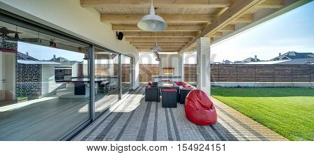 Tiled terrace zone next to the country house in a modern style on the wooden fence background. There is a brick furnace, a table and armchairs with red pillows, red pouf. On the right there is lawn.