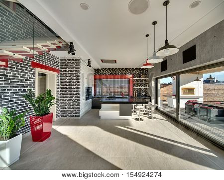 Modern interior with brick and concrete walls, large windows and tiles on the floor. There is a red-cream stair, plants in the pots, a kitchen zone with a bar. Outside there is terrace with furnace.