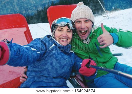 Happy skiers take a selfie photo on the top of mountain