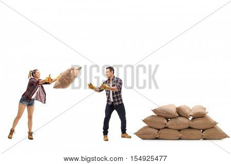 Female farmer throwing a burlap sack at a male farmer standing next to a pile of burlap sacks isolated on white background
