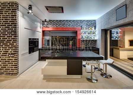 Contemporary kitchen with brick and concrete walls, large windows and the light tiles on the floor. There is a black kitchen island, a black tabletop with a sink and a bar, a built-in oven and chairs.