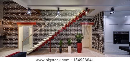Glowing room in a modern style with black brick walls and light tiles on the floor. There is a red stair with light wooden rungs and a glass partition, plants in the multi-colored pots and doors.