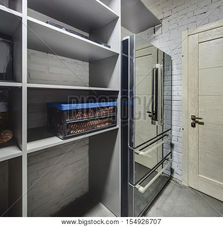 Pantry in a modern style with white brick walls and a gray floor. There is a big chrome fridge and gray cupboard with food. Lighting is artificial. Vertical.