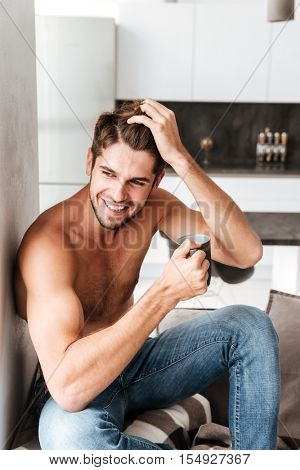 Happy shirtless young man sitting and drinking coffee on the kitchen