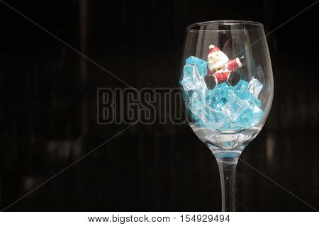 Still Life Photography With Santa Claus In A Glass Of Wine With Ice In Night Time With Dark Backgrou