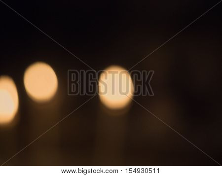 Blurred background of the three golden lights. Three out of focus goldy lights against blurred dark background.