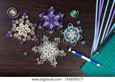 Handmade paper snowflakes with tools for quilling (paper strips slotted tool knife cutting mat) on dark wooden background. Preparation for Christmas.
