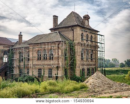 Picture of the old abandoned mansion-house with wooden trestle for alteration work. Verdurous mansion against the background of cloudy sky.