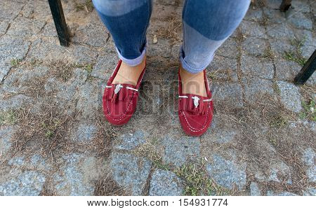 Womens legs in jeans and red loafers close up