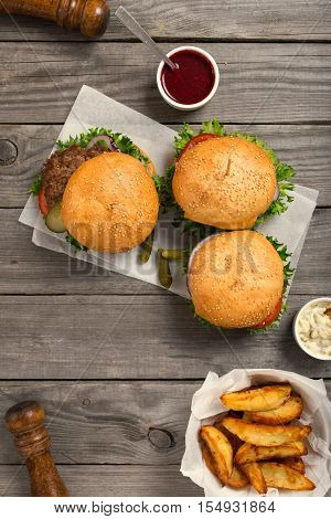 Burgers and cheeseburger on wooden table with sauces and fries top view