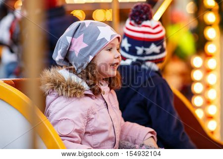 Adorable little boy and girl, siblings on a carousel at Christmas funfair or market, outdoors. Happy children, friends having fun. Selective focus on one child. Holiday, children, lifestyle concept.
